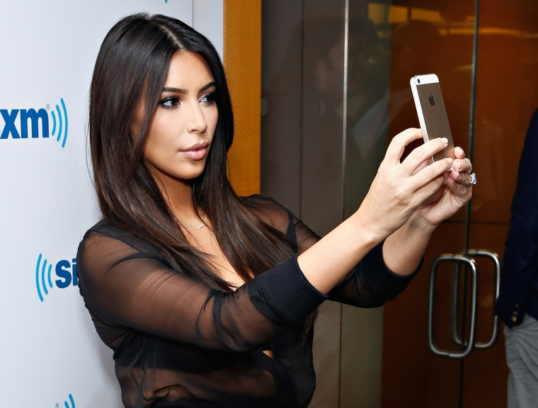 Kim Kardashian takes a selfie on the red carpet. (Photo Credit: Getty)